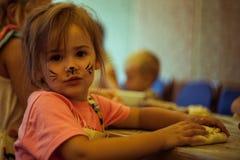 Klein meisje die eigengemaakte cake in een keuken met het art. van het kattengezicht koken Stock Afbeeldingen