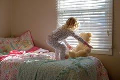 Klein meisje die haar teddybeer in de ochtend opnemen royalty-vrije stock fotografie