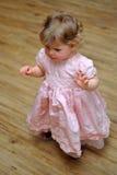 Klein meisje die zich in roze kleding op houten vloer bevinden Stock Foto
