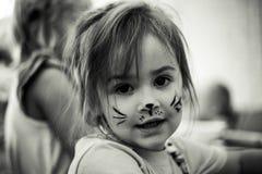 Klein meisje met de kunst van het kattengezicht, zwart-witte foto Stock Foto