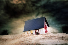 Klein model van huis in zand Stock Foto's