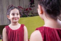 Klein mooi Arabisch meisje van het Middenoosten met vrij rode kleding en lippen die make-up zorgvuldig thuis in spiegel doen 8-10 Stock Fotografie