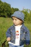 Klein mooi meisje op een gras Stock Foto