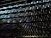 Klein oogje op zwarte metaalzonneblinden stock afbeeldingen