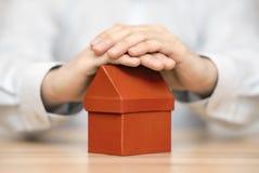 Klein oranje die huis door handen wordt beschermd Royalty-vrije Stock Afbeelding