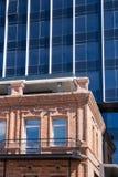 Klein oud baksteenhuis en de status van achter hem net de moderne bouw van glas en staal stock foto