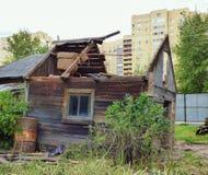 Klein oud beschadigd huis tegen moderne gebouwen stock foto