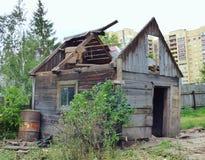 Klein oud beschadigd huis tegen moderne high-rise gebouwen royalty-vrije stock foto