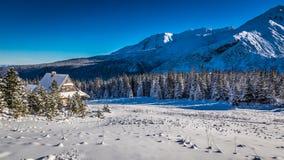 Klein plattelandshuisje bij de voet bergen in de winter Stock Afbeelding