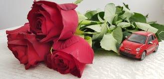Klein rood Fiat 500 stuk speelgoed op witte lijst dichtbij vijf rozenboeket stock afbeelding