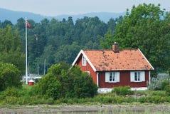 Klein, rood huis in Noorwegen Stock Foto's