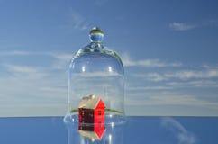 Klein rood huismodel in glasklok op spiegel in ruimte Royalty-vrije Stock Foto's
