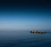 Klein rotsachtig eiland in oceaan Royalty-vrije Stock Afbeelding