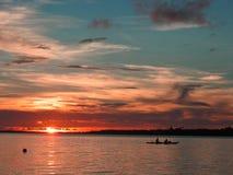 Klein schip die bij zonsondergang varen Stock Foto's