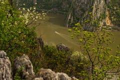 Klein schip die de Donau kruisen door hoge klippen Stock Afbeeldingen
