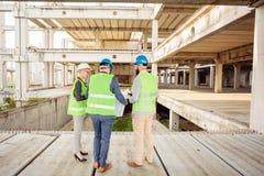Klein team van jonge ingenieurs die vorderingen in het werk betreffende een grote bouwwerf inspecteren stock foto