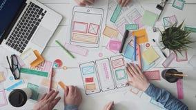Klein team van jonge UX-ontwerpers die mobiele app lay-out creëren stock videobeelden