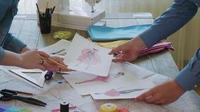 Klein team van manierontwerpers die schetsen voor de nieuwe kleding kiezen stock video