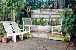 Klein tropisch huisbalkon met groene installaties in potten en witte bank stock afbeeldingen