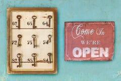 Klein uitstekend kabinet met geroeste hotelsleutels en open teken stock afbeeldingen