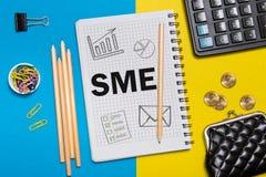 Klein und Mittelbetrieb, SME-Anmerkungen im Notizbuch auf dem Schreibtisch eines Geschäftsmannes im Büro Geschäftskonzept SME lizenzfreie stockbilder