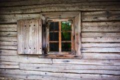 Klein venster in de muur van een oud blokhuis Stock Foto's