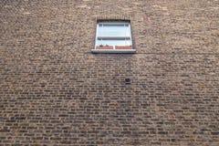 Klein venster in een grote bakstenen muur Royalty-vrije Stock Afbeeldingen