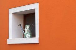 Klein venster met gieter Stock Foto's