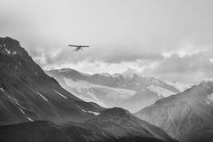 Klein vliegtuig in grote bergen Stock Afbeeldingen