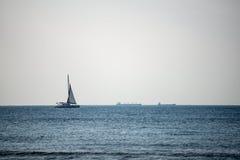 Klein wit schip in het overzees stock afbeeldingen