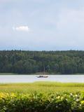 Klein, zeilboot die op een kalme rivier onder een humeurige hemel wordt verankerd Stock Foto
