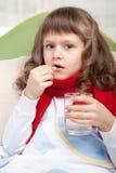 Klein ziek meisje met sjaal in bed Stock Afbeeldingen