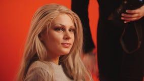 Kleinbetrieb - das junge blonde weibliche Modell, das für Fotografen aufwirft - arbeiten Sie Bühne hinter dem Vorhang um Stockfotografie