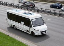 Kleinbus geht auf die Stadtstraße Lizenzfreie Stockfotografie