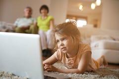 Kleindochter die laptop in woonkamer met behulp van Stock Fotografie
