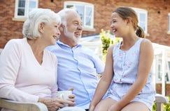 Kleindochter die met Grootouders tijdens Bezoek aan Pensioneringshuis spreken royalty-vrije stock fotografie