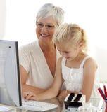 Kleindochter die met haar grootmoeder gegevens verwerkt stock fotografie