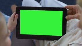 Kleindochter die oma mobiele apps op groene het schermtablet tonen, boodschapper stock video