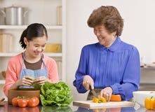 Kleindochter die salade met grootmoeder voorbereidt Stock Foto