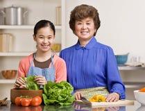 Kleindochter die salade met grootmoeder voorbereidt Stock Afbeeldingen