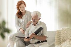 Kleindochter en gelukkig grootvader het letten op fotoalbum tijdens stock foto's
