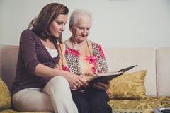 Kleindochter en grootmoeder die oude foto's bekijken stock foto's