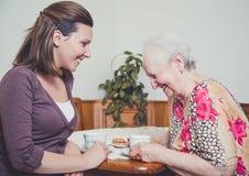 Kleindochter en grootmoeder die outloud lachen Stock Afbeelding