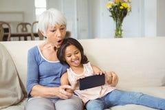 Kleindochter en grootmoeder die selfie op mobiele telefoon in woonkamer nemen royalty-vrije stock foto