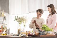 Kleindochter en grootmoeder het koken stock afbeeldingen