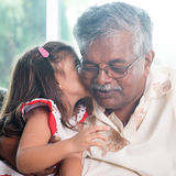 Kleindochter kussende grootvader Stock Fotografie