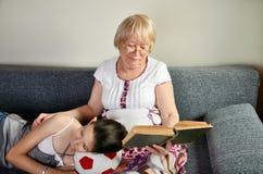 Kleindochter in slaap dichtbijgelegen haar lezingsgrootmoeder Royalty-vrije Stock Fotografie