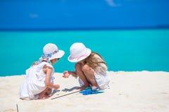 Kleine aanbiddelijke meisjes die beeld trekken op wit strand Leuke jonge geitjes op de zomervakantie in de Maldiven Stock Fotografie