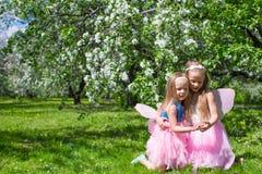 Kleine aanbiddelijke meisjes met vlinder onder vleugels Stock Foto