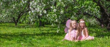 Kleine aanbiddelijke meisjes met vlindervleugels in Royalty-vrije Stock Foto's